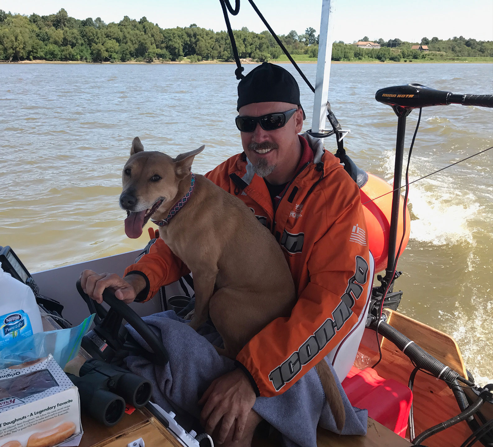 Marc Phelps holding dog Tula while driving the jon boat