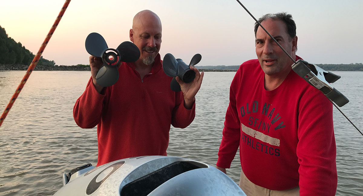 Marc Phelps changing the prop on his jon boat in the Mississippi River