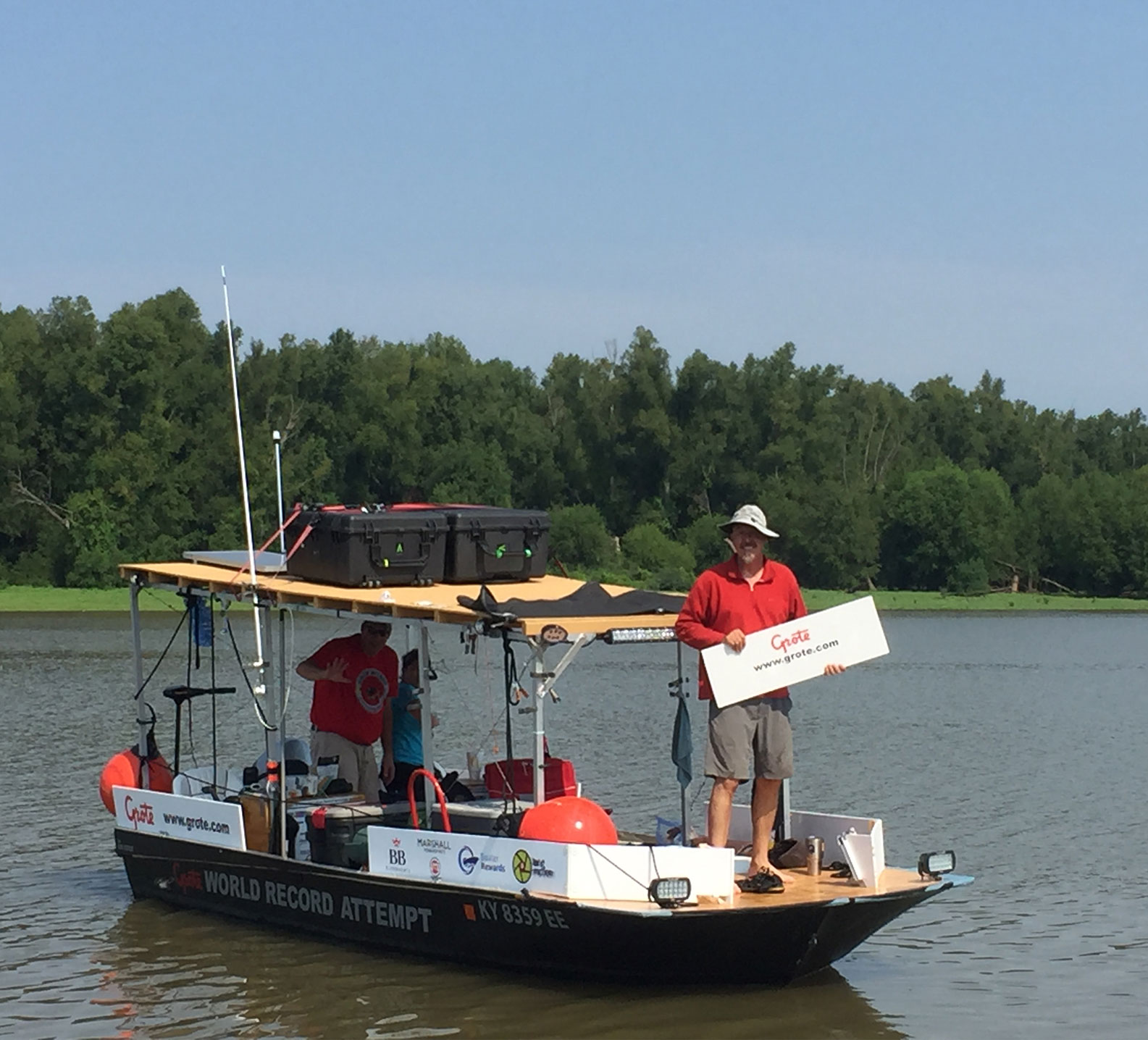 Marc Phelps holding up Grote sign on jon boat