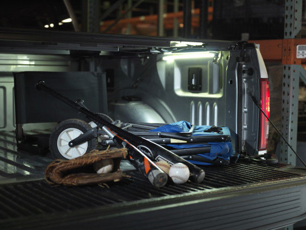 Truck bed lighting kit shining light on baseball equipment at night