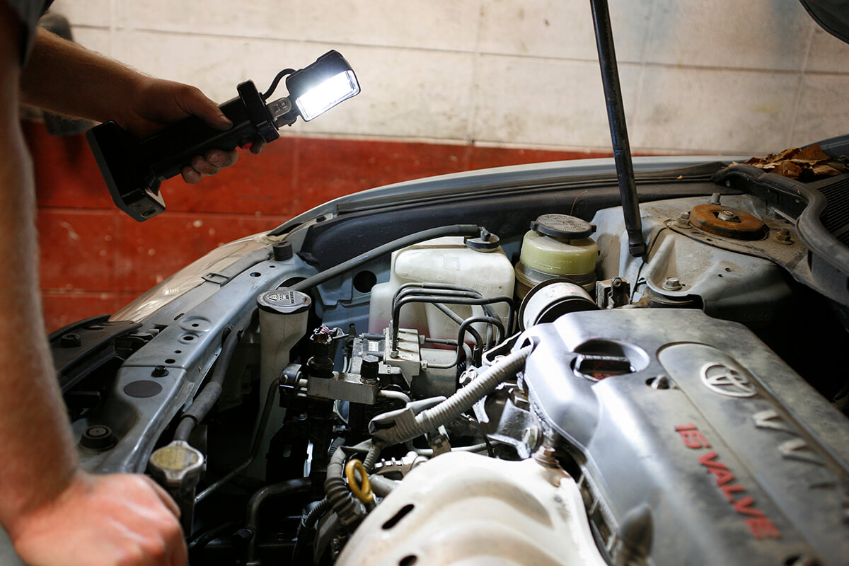 Mechanic using LED work light bz401-5 to look under car hood