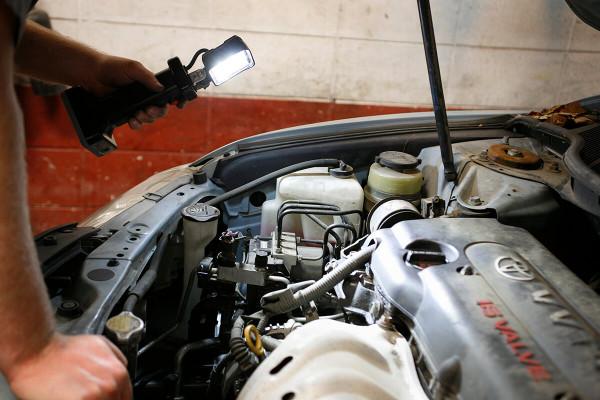 Mecánico usando luz de trabajo LED bz401-5 para ver debajo del capó de un auto