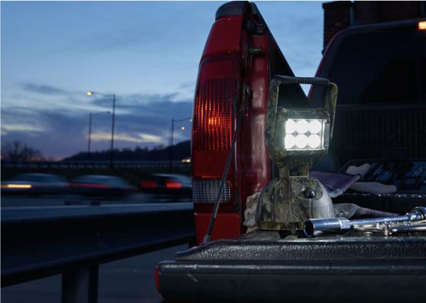 Luz LED camuflada usándose al cambiar la llanta de un camión de noche