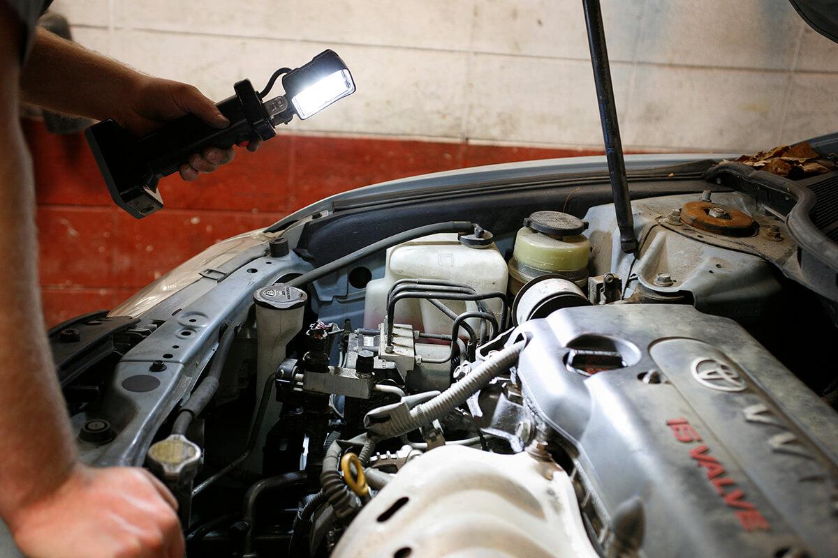 Mechanic using LED work light bz401-5 to look under car hood