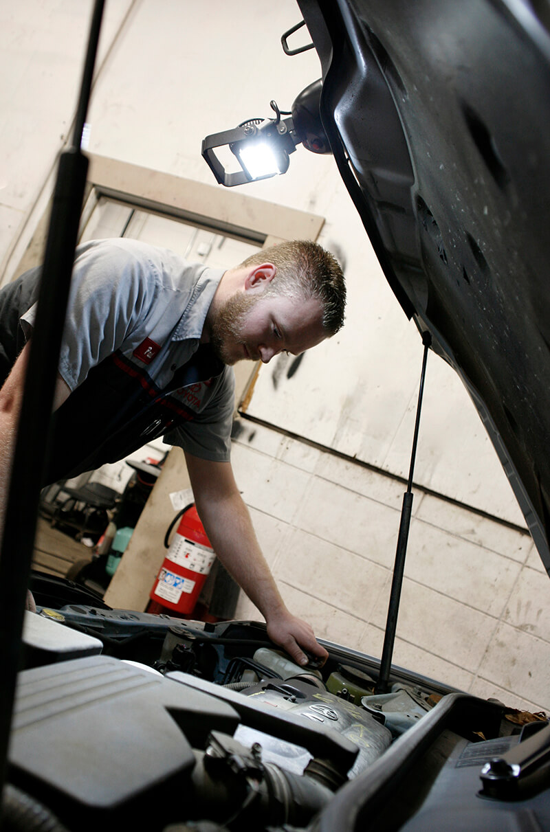 Mechanic using BriteZone LED work light to look under hood