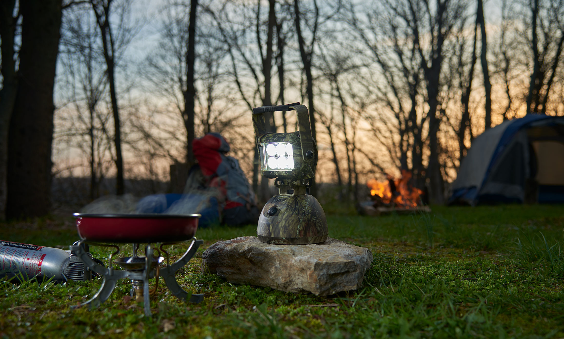 Camo LED Light sitting by a campfire